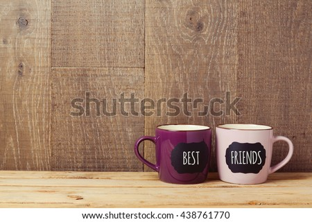 Coffee cups on wooden table with chalkboard sign and best friends text. Friendship day celebration background - stock photo