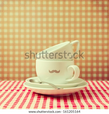 Coffee cups with hipster  mustache on checked tablecloth - stock photo