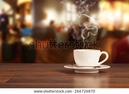 Coffee drink on wooden table with blur cafeteria as background - stock photo