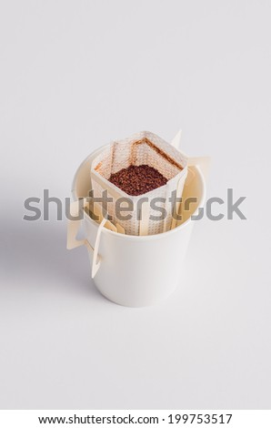 Coffee filled in a popup coffee-filter bag, isolated on white background