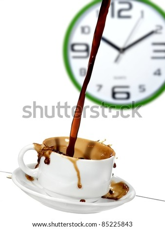Coffee flow in a cup with a  wall clock - stock photo