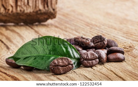 Coffee grains and green leaf on wooden background - stock photo