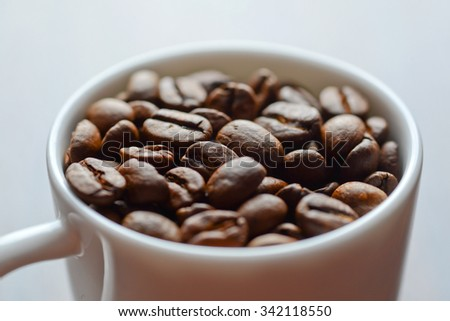 coffee grains in a white mug on a table