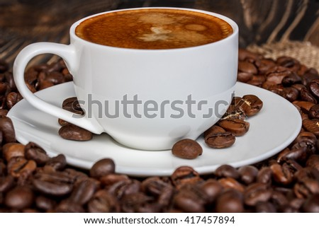 coffee grains on an old wooden board and a cup of coffee