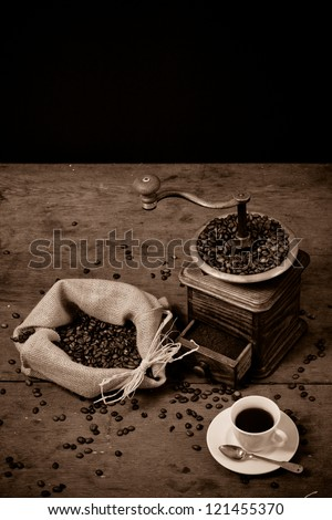 Coffee grinder (antique, XIX century), beans in canvas bag, cup and spoon on old oak table - stock photo