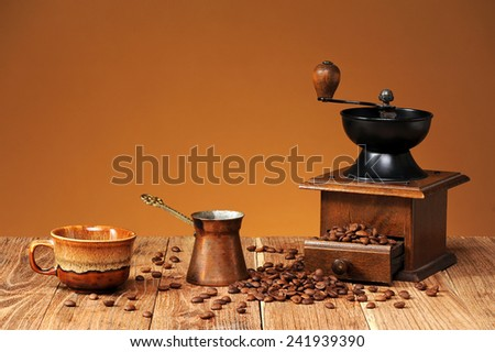 Coffee grinder, coffee pot and coffee grains from the table - stock photo