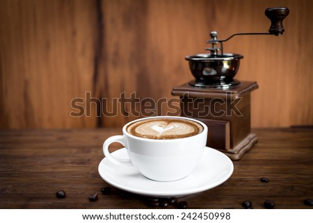 Coffee grinder, cup of coffee on brown wooden background - stock photo