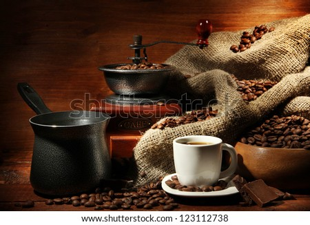 Coffee grinder, turk and cup of coffee on brown wooden background - stock photo