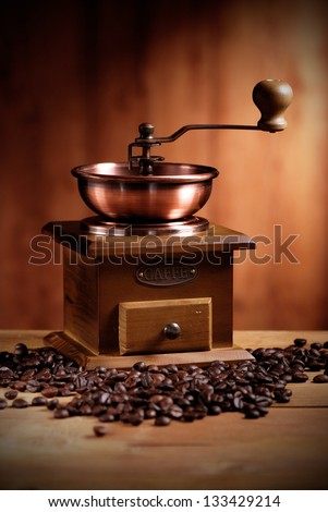 coffee grinder with coffee beans on wooden table - stock photo