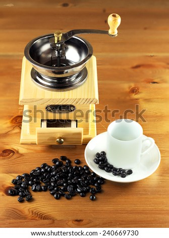 coffee grinder with coffee beans on wooden table