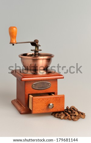 Coffee grinder with coffee beans vertical on a gray background