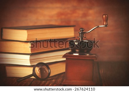 Coffee gringer and ropened book on wooden background.