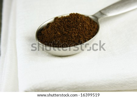 Coffee grounds in a measuring spoon on a white cloth.