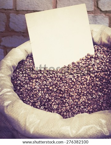 Coffee grunge concept with a paper note for text, vintage colors with a soft light. Coffee beans in retro style. Big sack with roasted coffee beans, toned image of the instagram filter effect. - stock photo