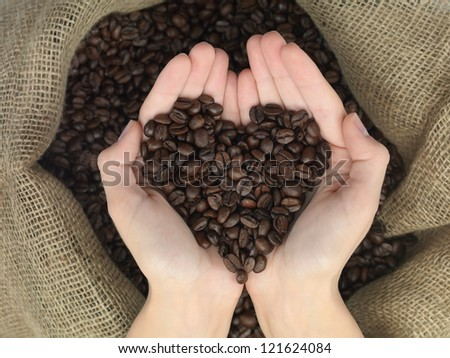 coffee heart shape held in hands over a canvas bag - stock photo