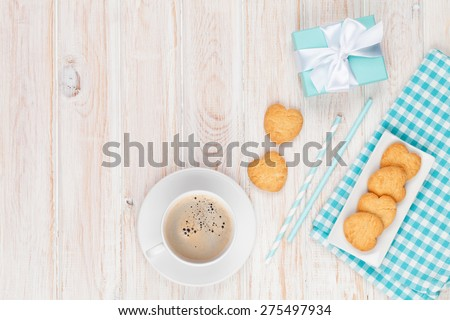 Coffee, heart shaped cookies and gift box on white wooden table with copy space - stock photo