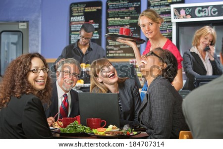 Coffee house barista serving laughing business people - stock photo