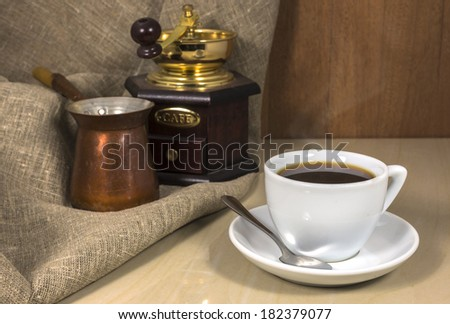 Coffee in a cup on a marble table, coffee grinder and Cezve