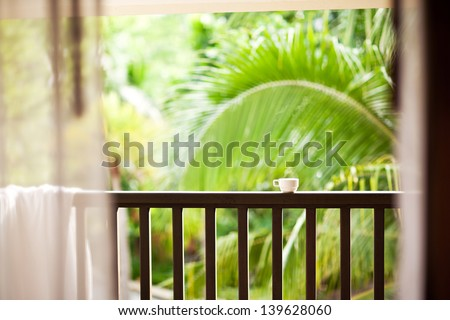 Coffee in a cup on balcony with nature and palm - stock photo