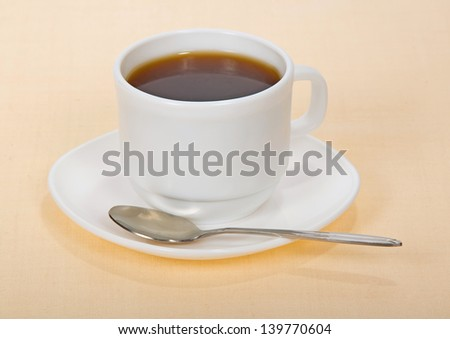 Coffee in a cup with a saucer, on a beige background - stock photo