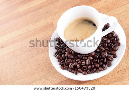 Coffee in a cup with beans - stock photo