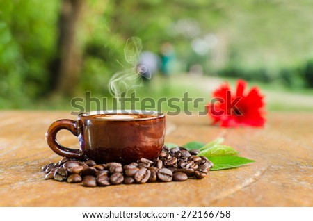 Coffee in a mug & beans with flower and leaves - stock photo