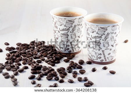 Coffee in a paper cup with coffee beans - stock photo