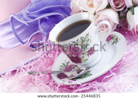 Coffee in a pretty feminine rose print fine china cup with ladies hat and roses in background with copy space - stock photo