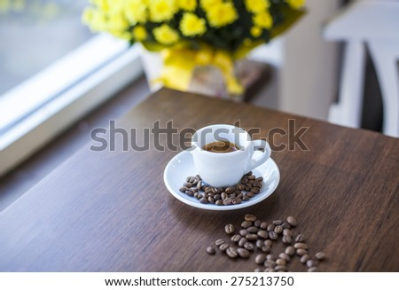 Coffee in a white cup and baked beans on a wooden table - stock photo