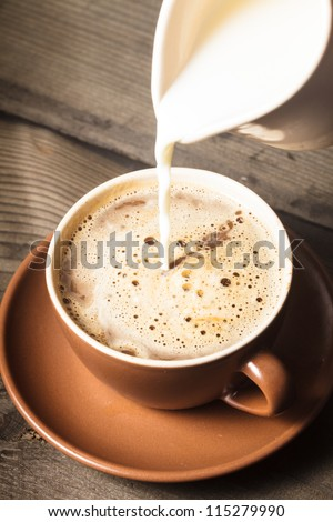 Coffee in brown cup and milk on wood background closeup - stock photo