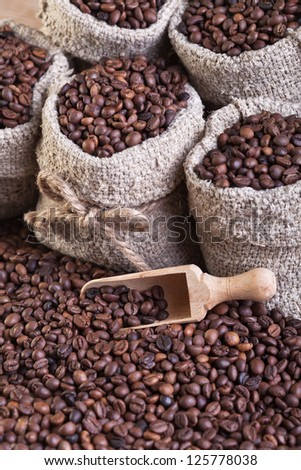 Coffee in burlap bags and spilled on the table - closeup - stock photo