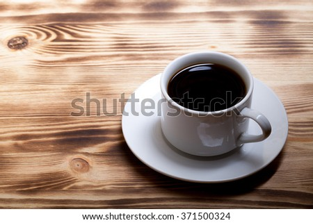 Coffee in cup on light wooden table.