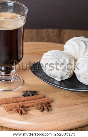 Coffee in glass cup and cinnamon with zephyr on wooden table