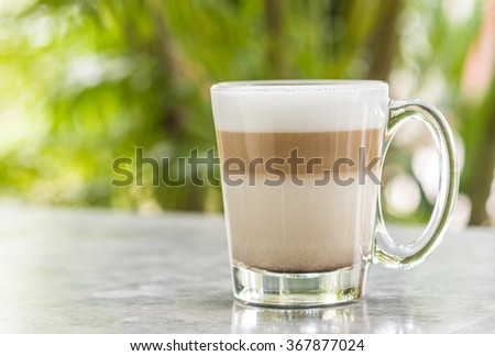 Coffee in glass on blurred marble chair and green tree bokeh background - stock photo