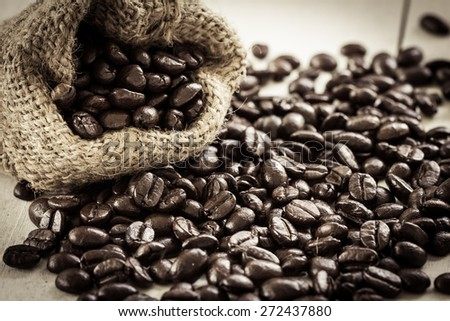 Coffee in love,coffee in cup with roasted coffee bean heart shape on wooden background in sweet color filterd - stock photo