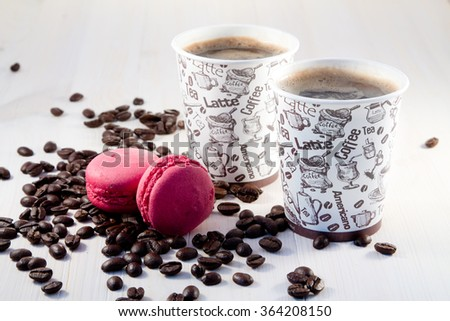 Coffee in paper cups and macaroon - stock photo