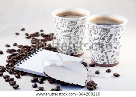 Coffee in paper cups with coffee beans and notepads - stock photo