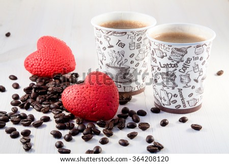 Coffee in paper cups with coffee beans and red hearts - stock photo