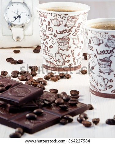Coffee in paper cups with coffee beans, white clock and tiles of dark chocolate - stock photo