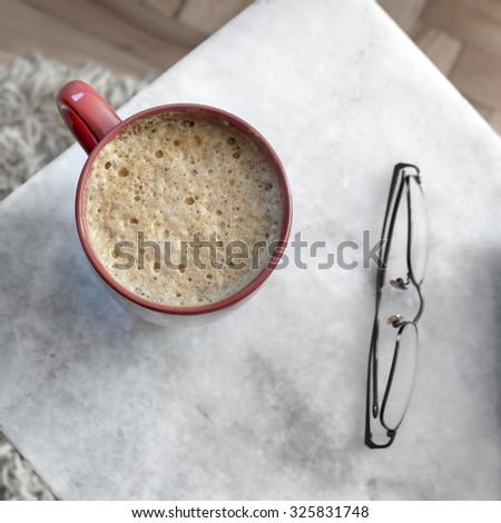Coffee in red cup  on a marble table, from above - stock photo