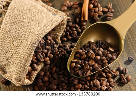 Coffee in  sack and scoop on wooden table - stock photo