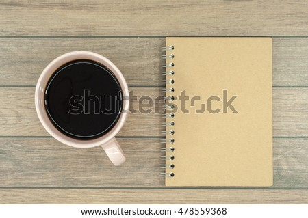Coffee in the cup and note book on the wooden desk