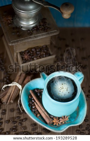 Coffee in the teal mug and old coffee mill with cinnamon and star anise. Selective focus. - stock photo