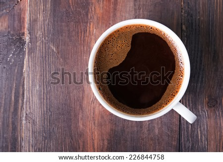Coffee in the white cup on the wooden table, top view - stock photo