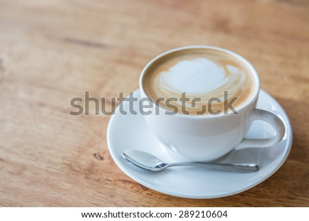 Coffee in white cup on wood table - stock photo