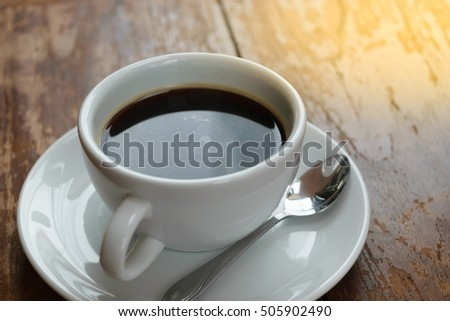 Coffee in white cup on wood table , process in soft orange sun light style