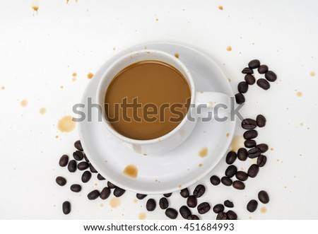 coffee in white cup with coffee beans and coffee stain