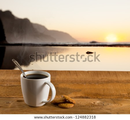 Coffee in white pottery cup on old wooden table with blurred image of kauai coast ocean at sunset or sunrise - stock photo