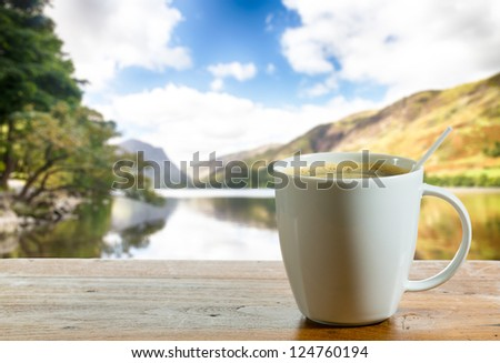 Coffee in white pottery cup on old wooden table with blurred image of lake district in England as background - stock photo