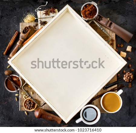 Coffee ingredient frame with place for text or recipe. Coffeee beans and ground coffee with spices and accessories on rustic background.